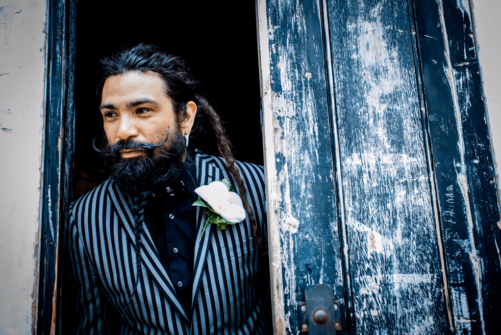 The groom was wearing a striped suit, a black shirt, a crazy hairstyle and a braided beard with a moustache