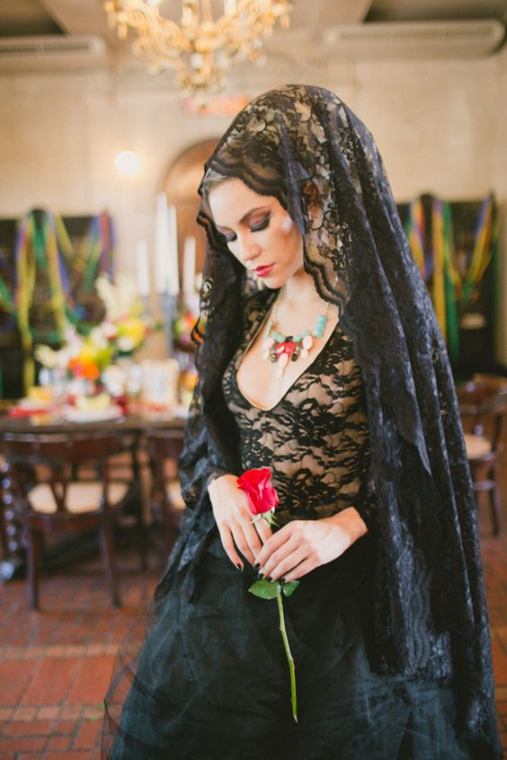 a black lace wedding gown and a black lace veil for a Day of The Dead wedding