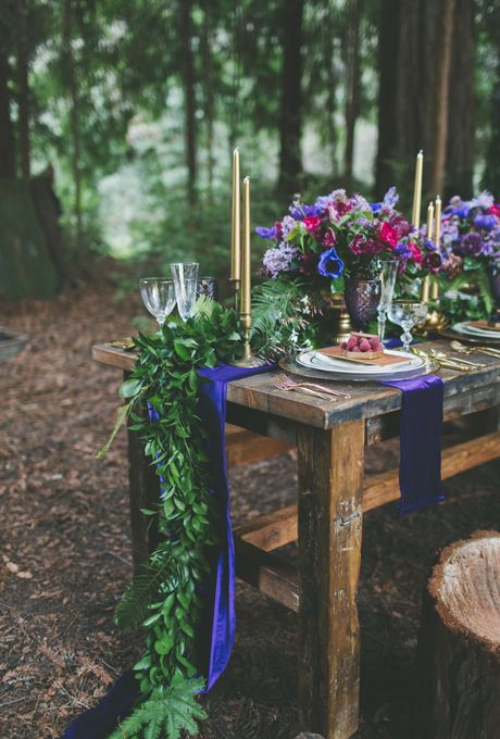 a bold purple runner and a greenery one over it for a jewel-tone wedding
