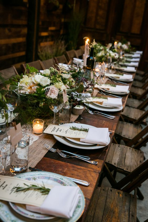 a rustic table setting with a burlap and lace table runner, evergreens and blooms, candles