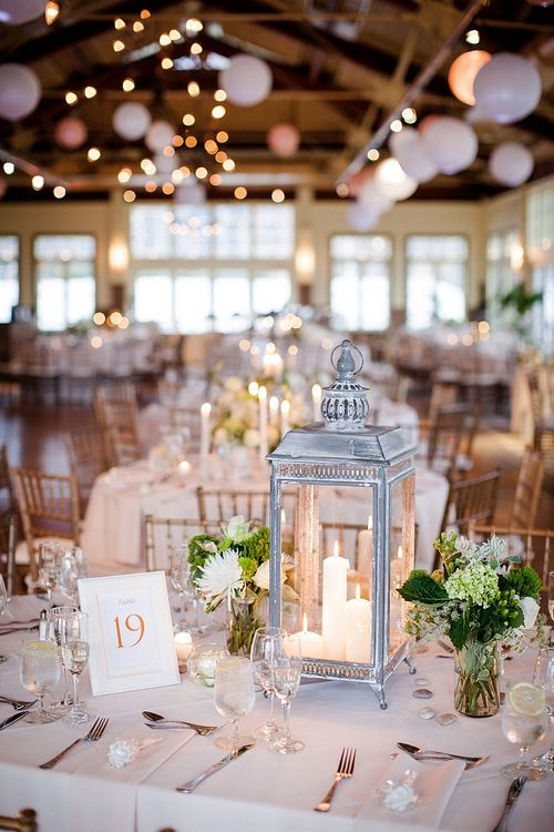 A Whitewashed Lantern With Candles And Some Green White Flroal Arrangements