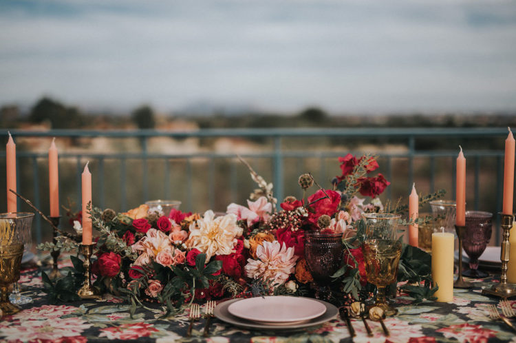 The centerpiece is stunning, moody with soft blush and hot red blooms