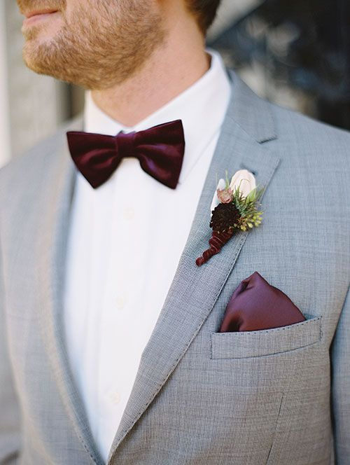 a grey two piece wedding suit with a maroon handkerchief, bow tie and boutonniere
