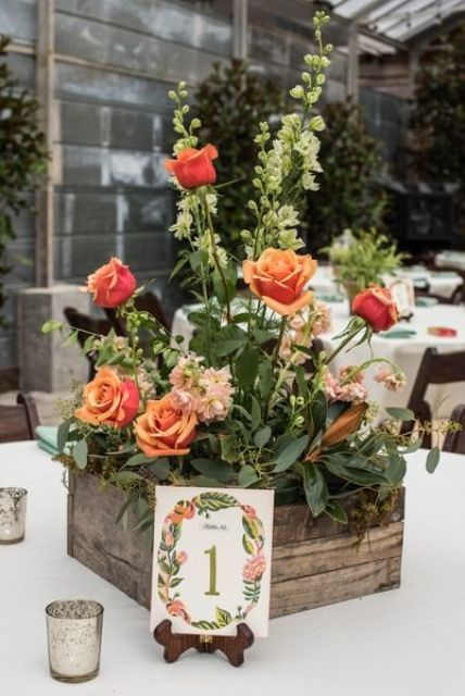 a pallet wood ox with greenery and orange roses for a cool garden wedding
