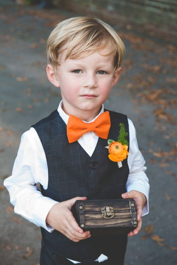 A Ring Bearer In Navy Waistcoat White Shirt And An Orange Bow Tie