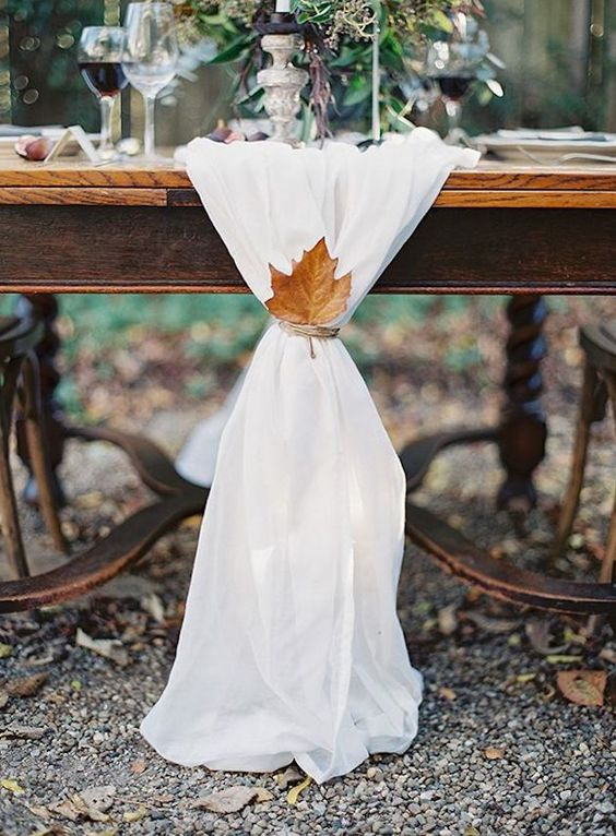 a simple white fabric table runner with twine and a fall leaf can be enough