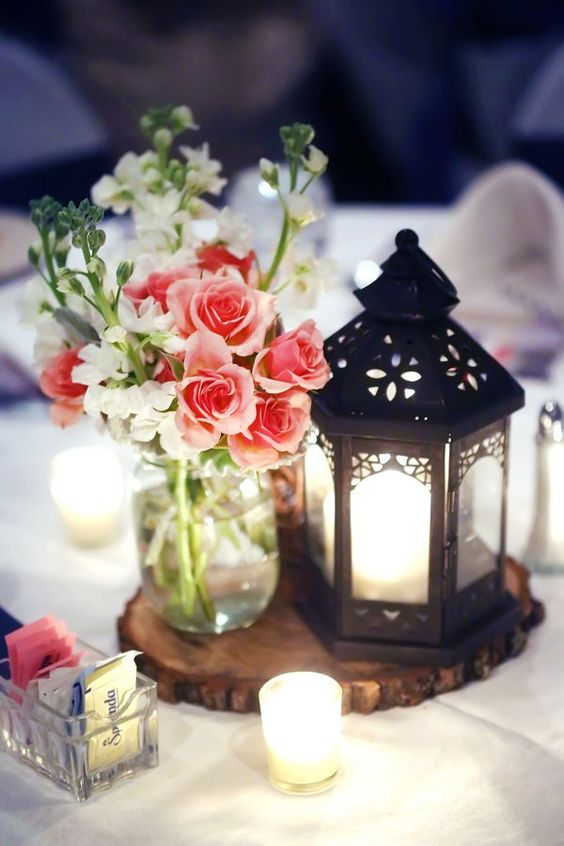 a wood slice with a pink floral arrangement and a black candle lantern can fit a rustic wedding table