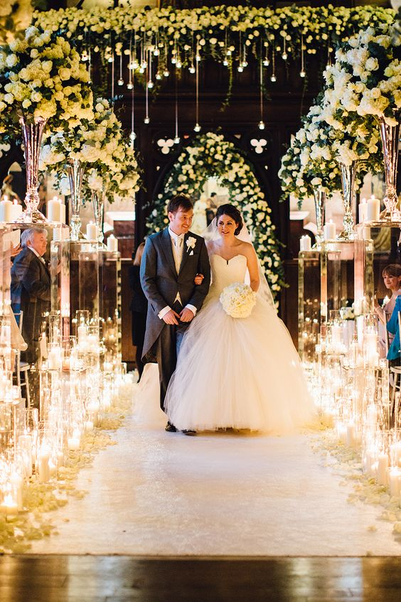 light up your wedding ceremony space with lots of candles and add lush florals to highlight the gorgeous venue
