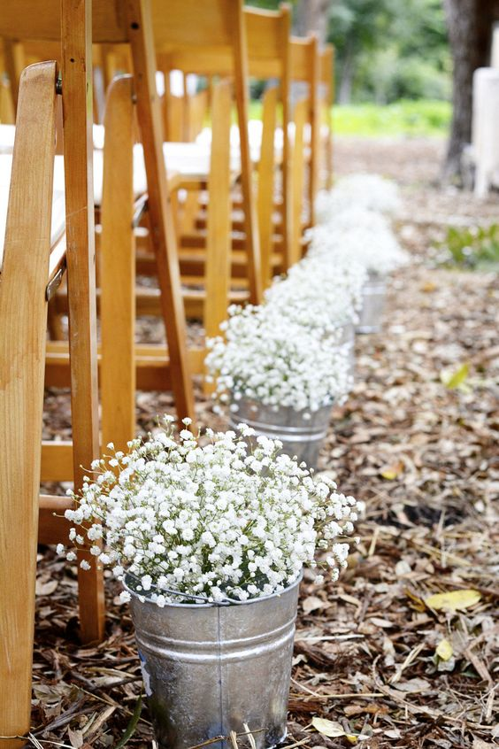 wooden chairs and buckets with baby's breath for a ranch wedding aisle