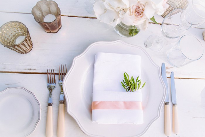 The table setting was white and blush, with neutral florals and some glam touches
