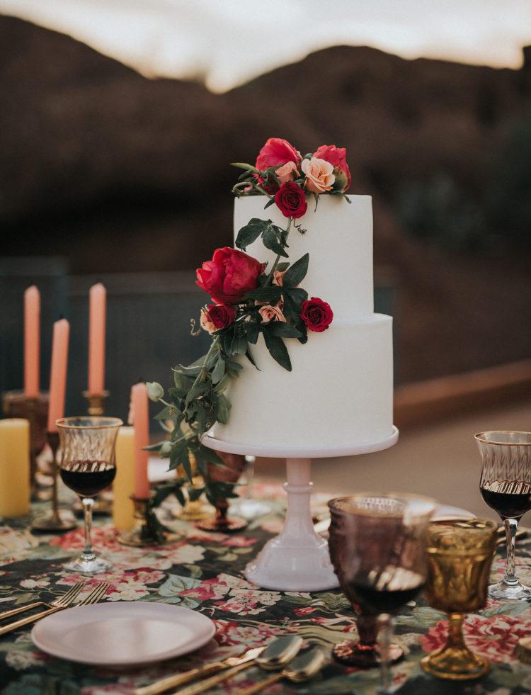 Die Hochzeitstorte in reinweiß und heiße rote Rosen auf Spitze