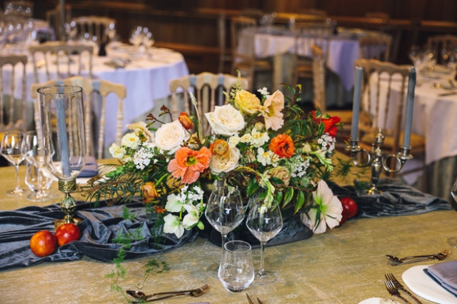 The wedding tablescape featured a grey velvet table runner, apples and a bold orange centerpiece that reminded of Dutch Masters' still lifes