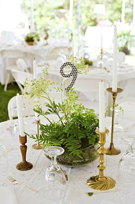 a glass bowl with greenery and herbs and a black and white table number for a woodland wedding