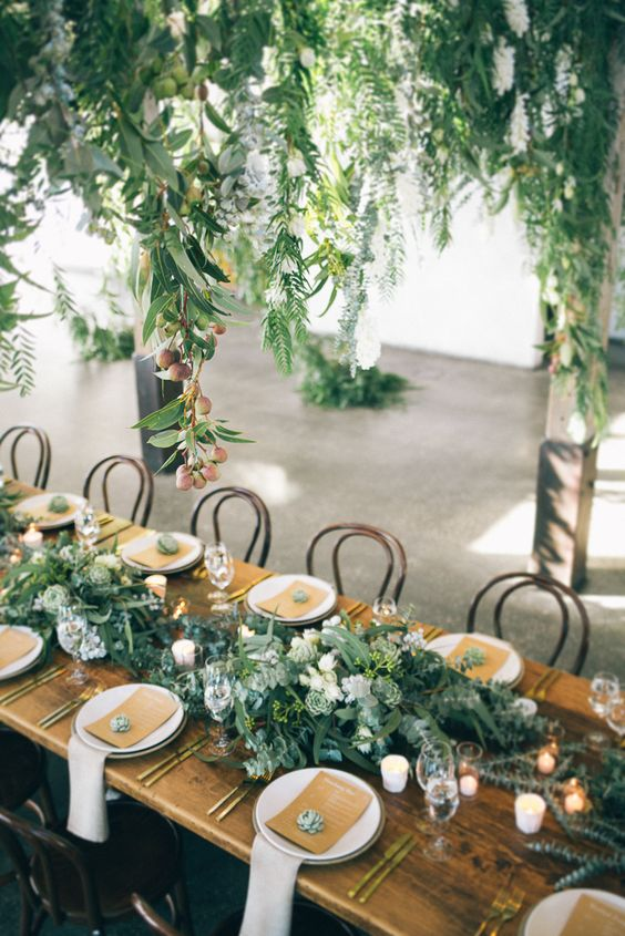 a lush greenery and white bloom table runner, no tablecloth, gold flatware and succulents