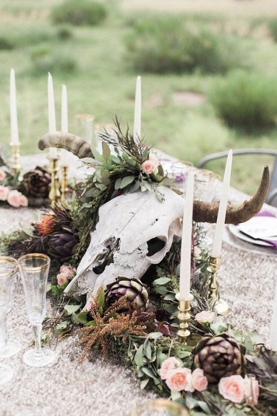 a moody wedding centerpiece with candles, artichokes and greenery for a boho wedding