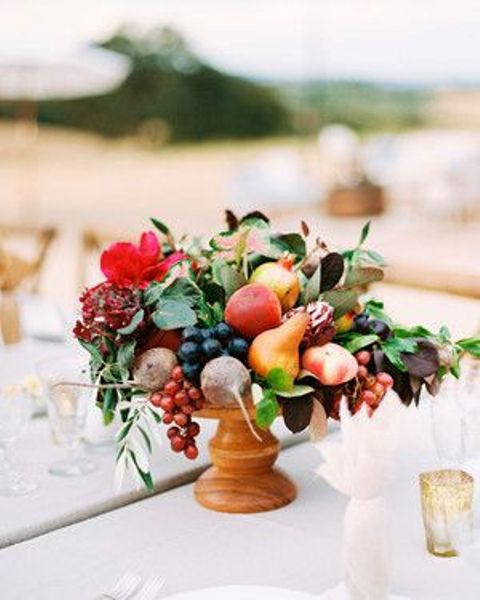 a summer centerpiece with grapes, pears, apples and beets and some bold blooms and leaves