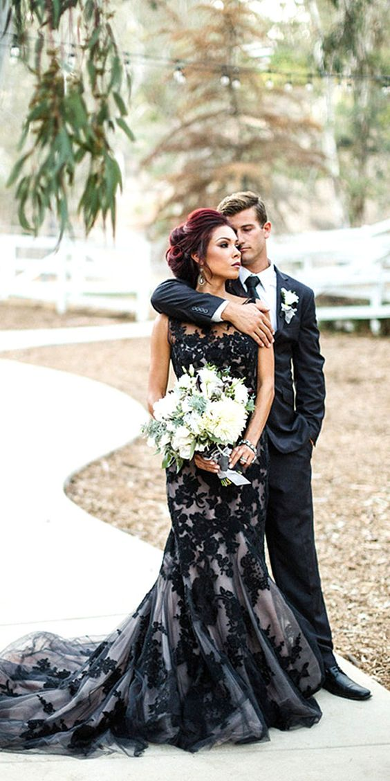 a trumpet wedding dress with a black lace layer over the neutral gown for a dramatic look
