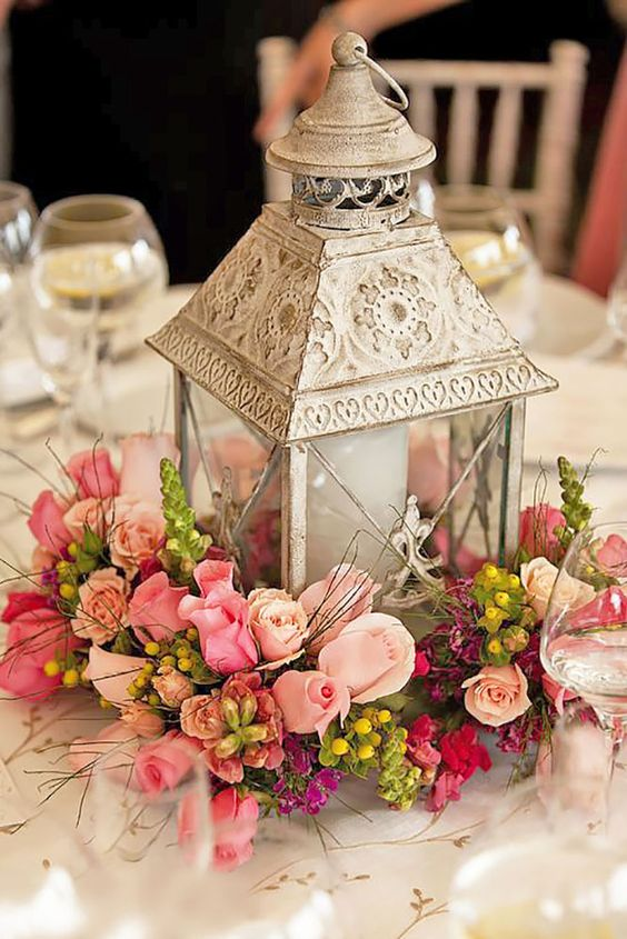 a whitewashed metal candle lantern on a pink floral arrangement for a shabby chic feel