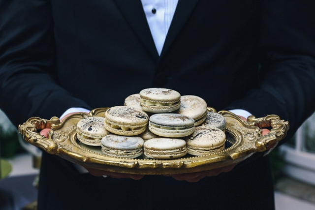 Large gold leaf macarons with cream inside as refined desserts