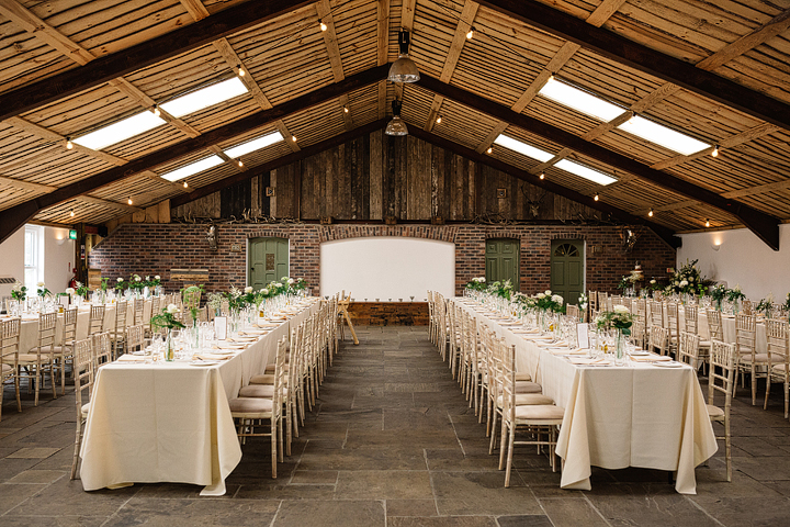 The barn was simply and elegantly decorated with greenery, white roses and rustic touches