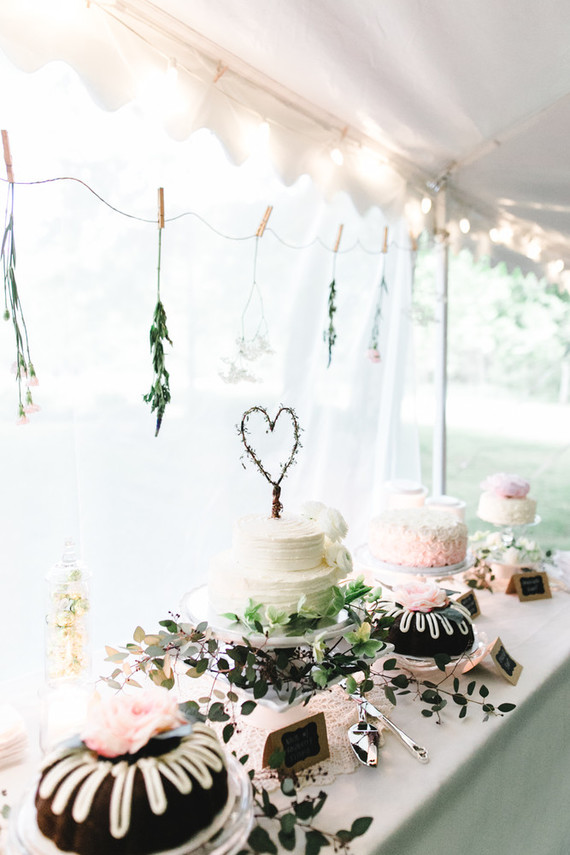 The cake table with an assortment of cakes and bundt cakes topped with cream and fresh blooms