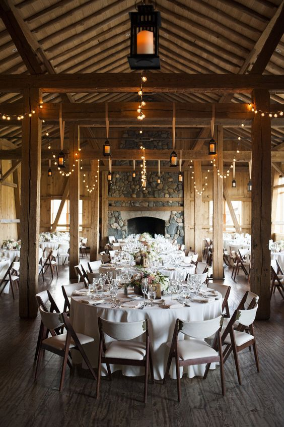 a cozy wood barn with a stone fireplace and lots of candle lanterns