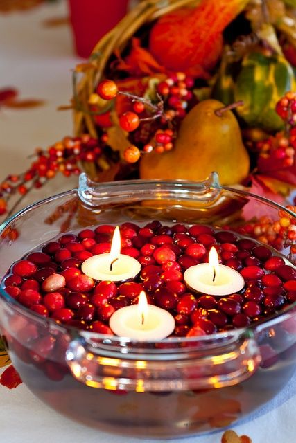 a glass bowl with cranberries and floating candles for a fall or winter wedding