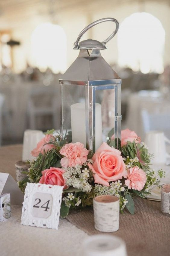 a shiny candle lantern with a coral rose and succulents arrangement and candles around looks trendy