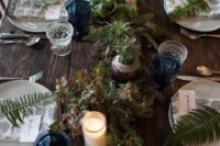 10 a wooden table with a greenery table runner, potted plants, candles and fern leaves for each place setting