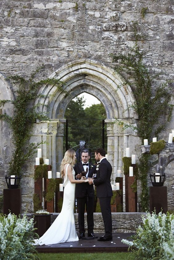 wedding ceremony in front of one of the Irish castles, a moody feel is achieved with a moss and candle backdrop