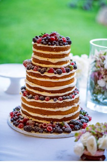 The wedding cake was naked and topped with fresh berries