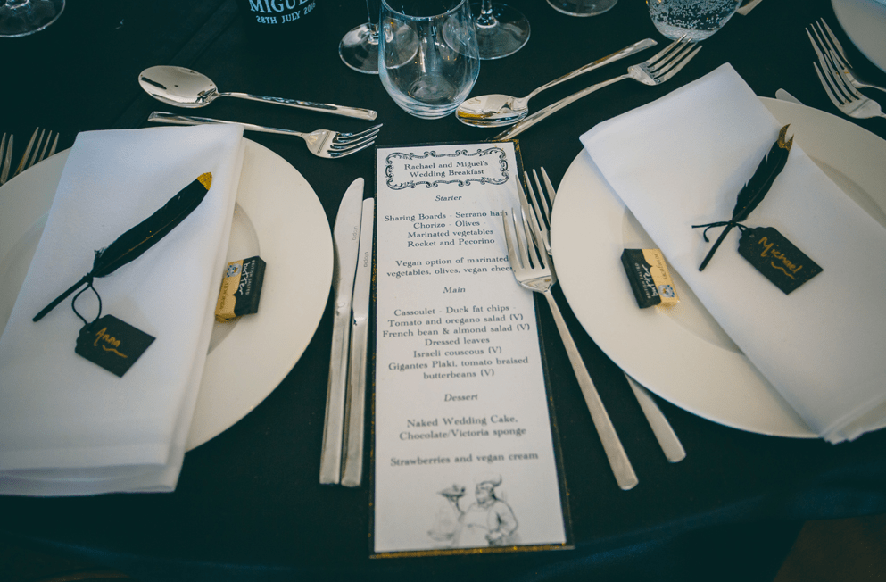 The wedding table setting was done in black and white, and each place setting was decorated with gold dipped black feathers