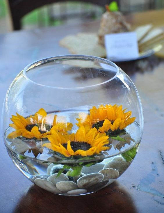 a bowl with pebbles and floating sunflowers is great for a rustic summer wedding