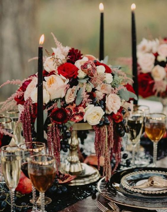 a lush decadent centerpiece with neutral, blush, red blooms and black grapes looks boho lux and jaw dropping