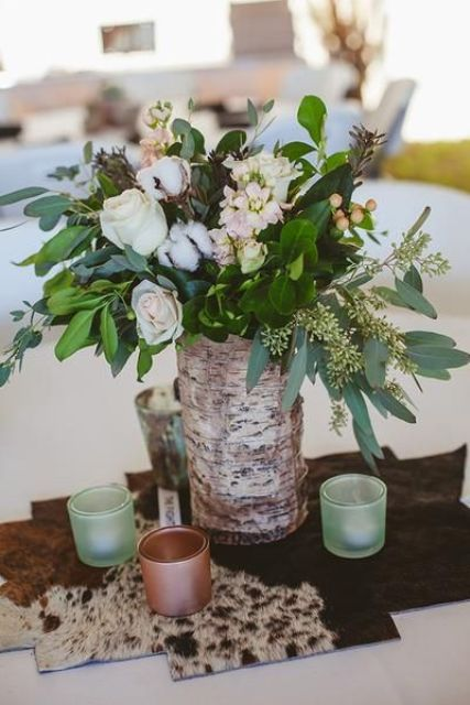a wedding centerpiece with a cow skin, copper and mint candle holders, a bark centerpiece with greenery, white roses and cotton