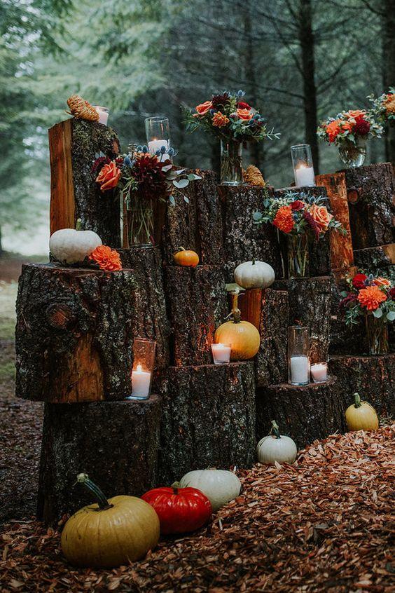 a wood stump wall with candles, fall floral arrangements and pumpkins as a rustic wedding backdrop