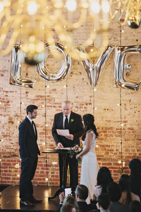 string lights and oversized LOVE balloons for an industrial wedding ceremony