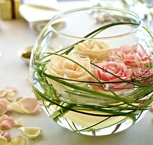 a bowl with greenery and floating roses in blush and pink is ideal for a garden wedding