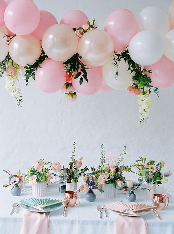 a pink and cream balloon, flower and greenery garland hanging over the reception
