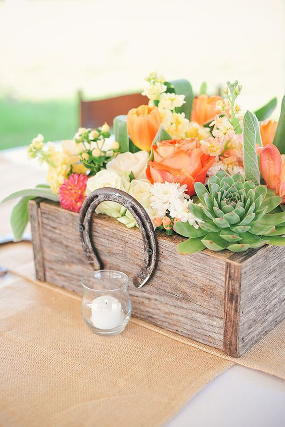 a reclaimed wooden box with bold florals and succlents, topped with a horse shoe for a rustic or backyard wedding
