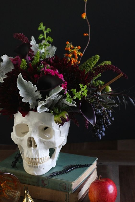 a skull vase with pale greenery, burgundy and deep plum purple blooms for a centerpiece