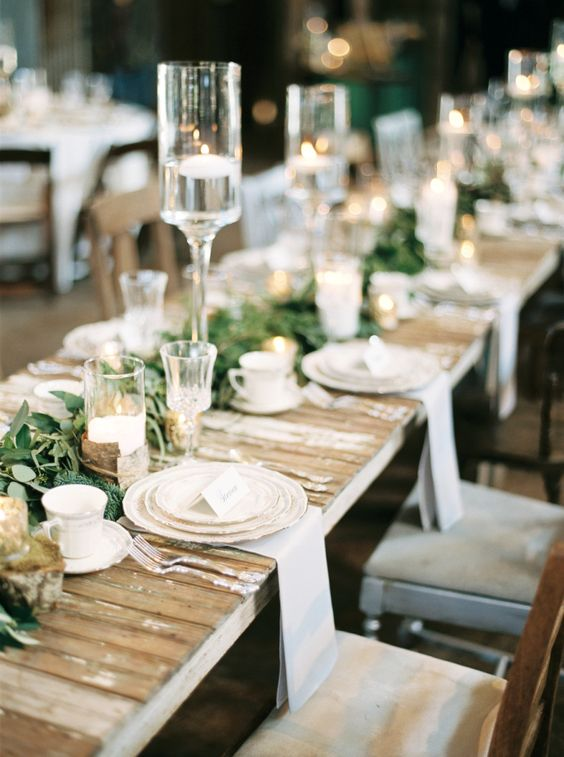 a wedding reception with pallet tables, greenery table runners, candles for a cozy feel