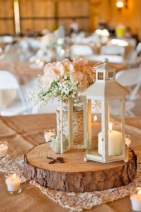 a wood slice with a white candle lantern and a rustic floral arrangement in a jar wrapped with lace