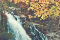 12 fall forest with a waterfall and a beautiful couple next to it