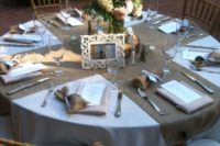 12 simple rustic table setting with burlap table runners, a wood slice and a floral centerpiece