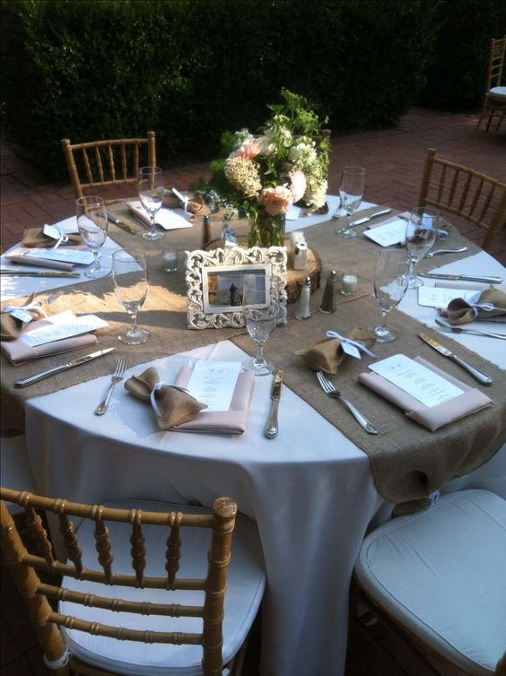 simple rustic table setting with burlap table runners, a wood slice and a floral centerpiece