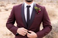 13 a two piece burgundy suit with black touches and a black tie