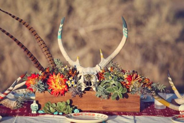 a wooden box centerpiece with bold blooms, succulents, feathers and a skull for a boho wedding