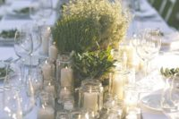 13 multiple jars with candles, potted herbs and greenery and a burlap runner