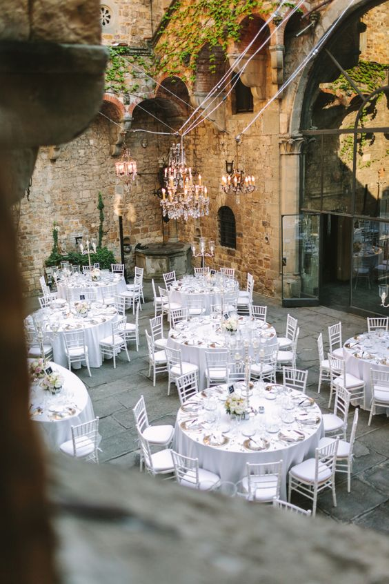 refined all-white wedding reception in a castle inner courtyard looks romantic and glam